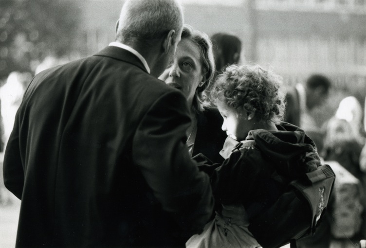 A curly haired boy - his face lit up by the sun - sitting on the arm of his mum. His mum is talking to a gentleman with his back to the camera.