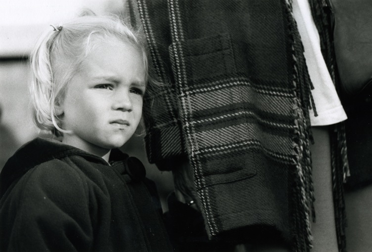 A very blond little girl standing next to her mom. Mom is wearing a checked coat.