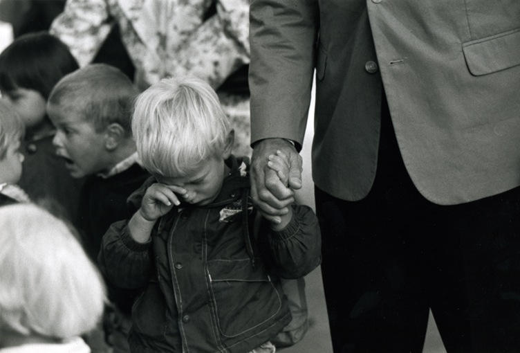 A little boy wiping a tear from his eye while holding the hand from his father. In the background another boy is shouting exictedly into the face of another child.